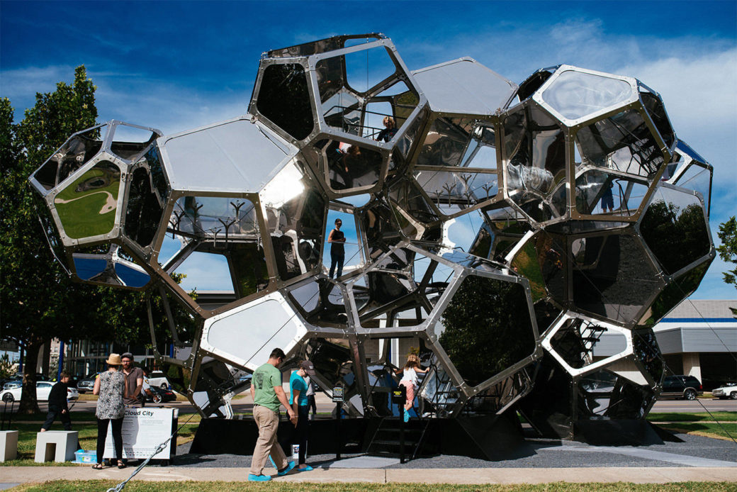 A photo of a large glass and metal sculpture with various compartments for people to climb in and through
