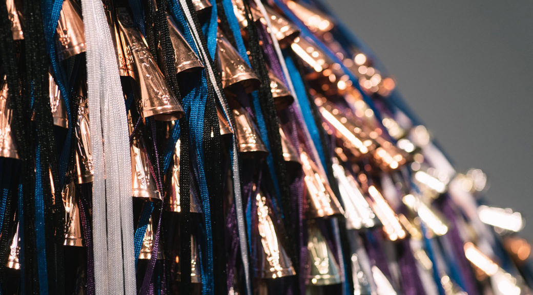 Copper-colored bells are interspersed with tassels and beads of blue, white, black and purple
