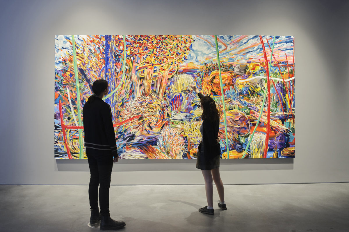 Two figures in silhouette stand in front of a large, brightly painted canvas.