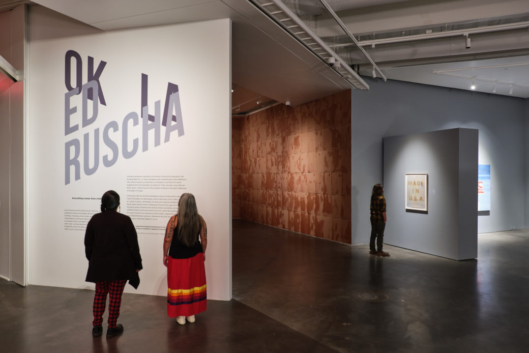"""People view works in an art gallery with polished concrete floors. A wall says """"OK LA ED RUSCHA"""""""