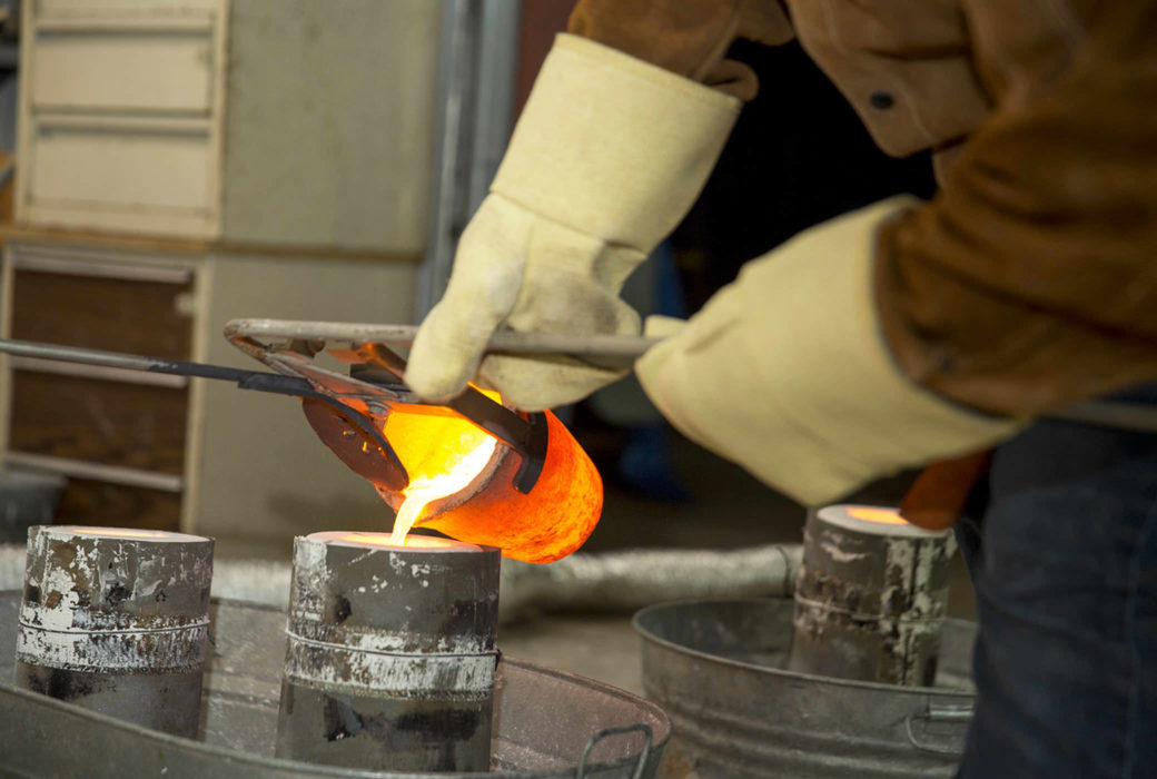 A standing figure pours a molten liquid into a mold
