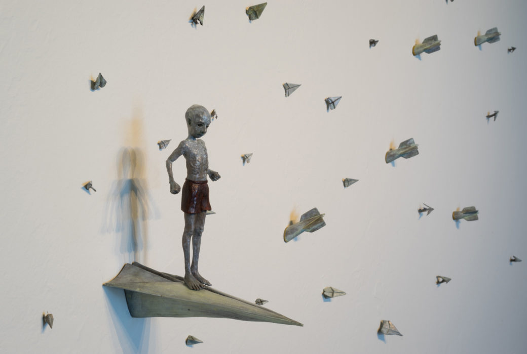 A small figurine standing on a replica of paper airplane while other planes dot the wall around him