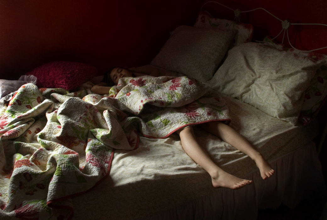 A small child lays across a bed with a blanket, thier feet hang off the edge