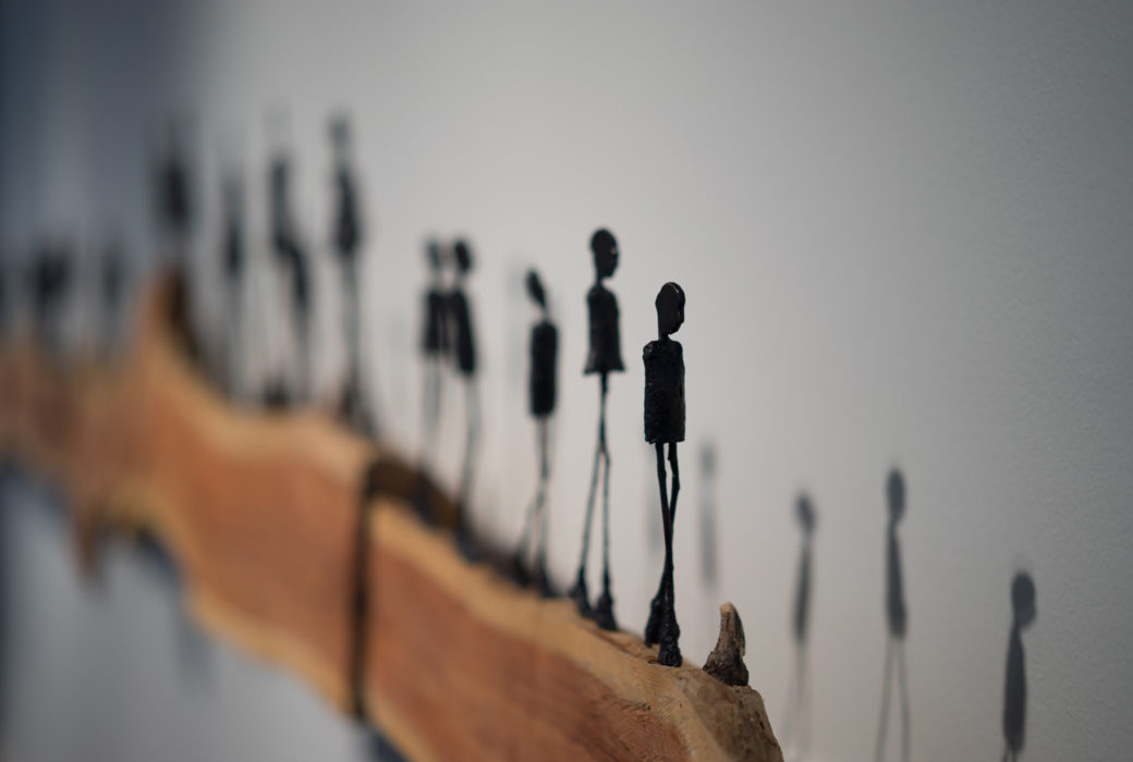 A sculpture of stick figure silhouettes standing on a plank of treated branch