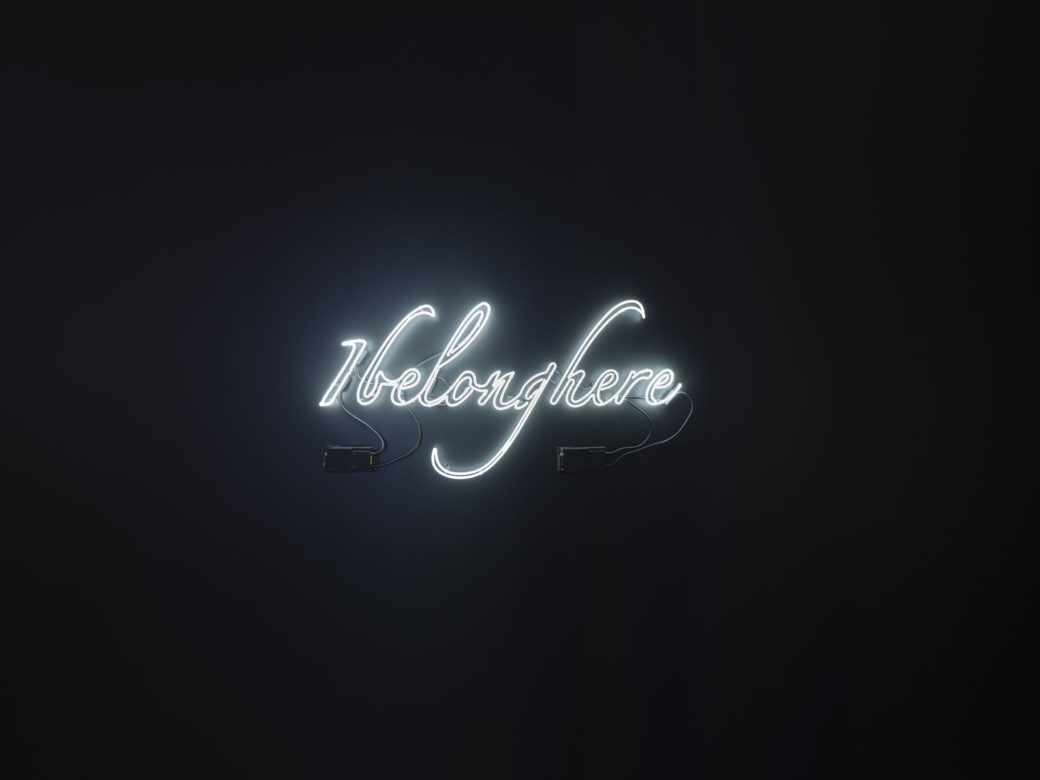 "A wall-mounted sculpture constructed of white fluorescent lights against a black wall that reads ""I belong here"""