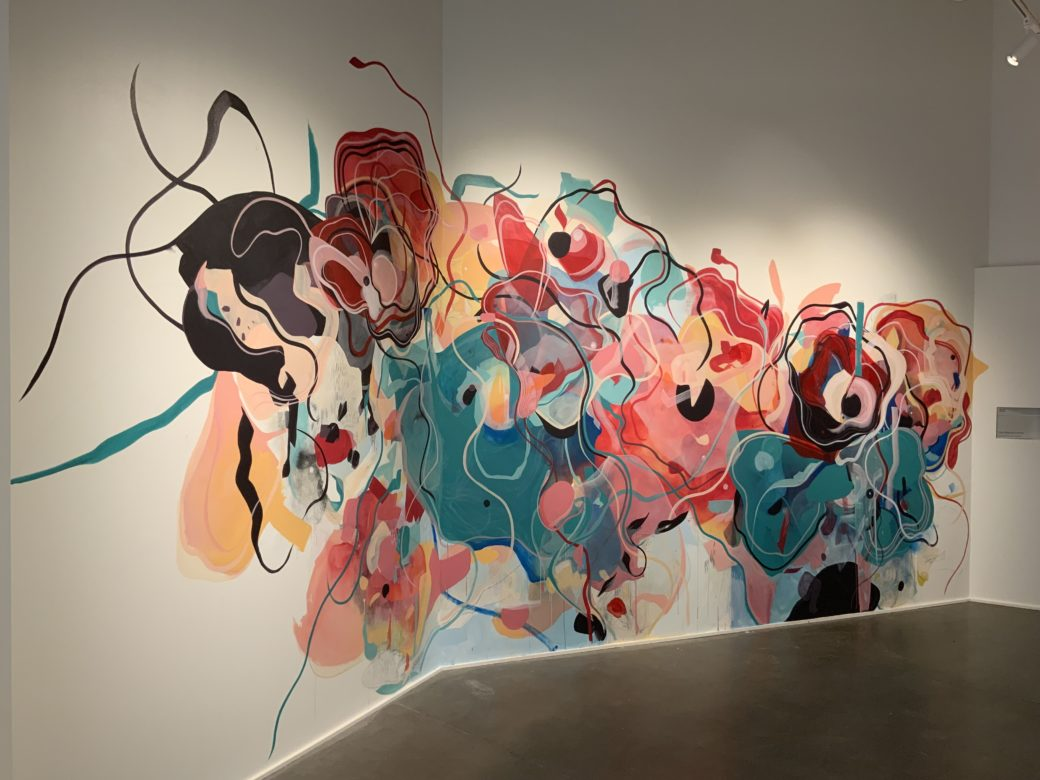 Abstract mural featuring freeform shapes in teals and rich pinks with vine-like lines throughout in a white-walled gallery with concrete floors