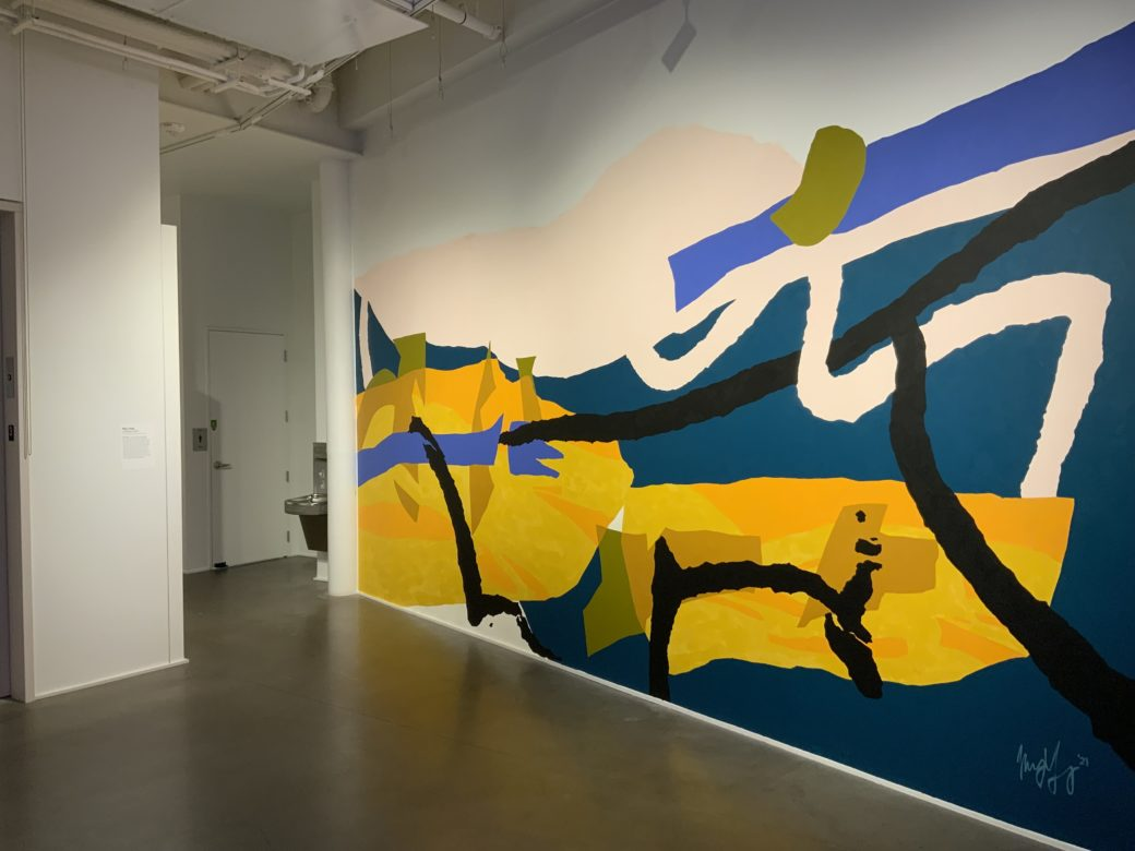 Abstract mural featuring large blocks of cool blue and warm yellow colors and fluid black and cream lines in a white-walled gallery with concrete floors