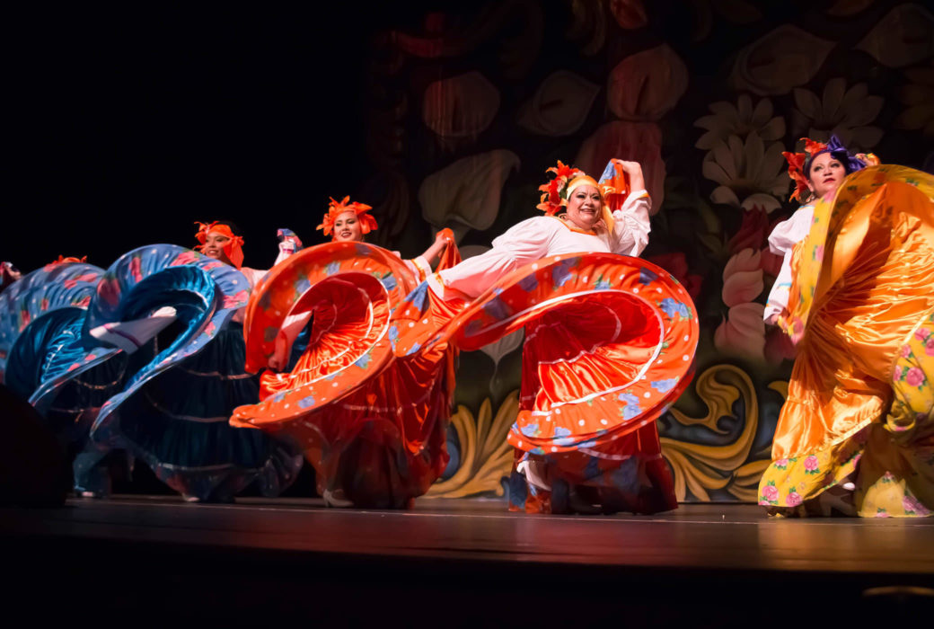 Several mariachi dancers are photographed mid-movement while their colorful skirts twist through the air