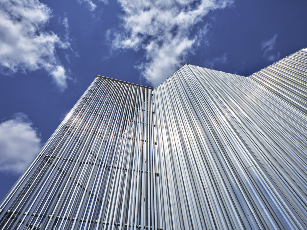 The corner edge of a contemporary building covered in silver aluminum fins, set against a blue sky with white clouds
