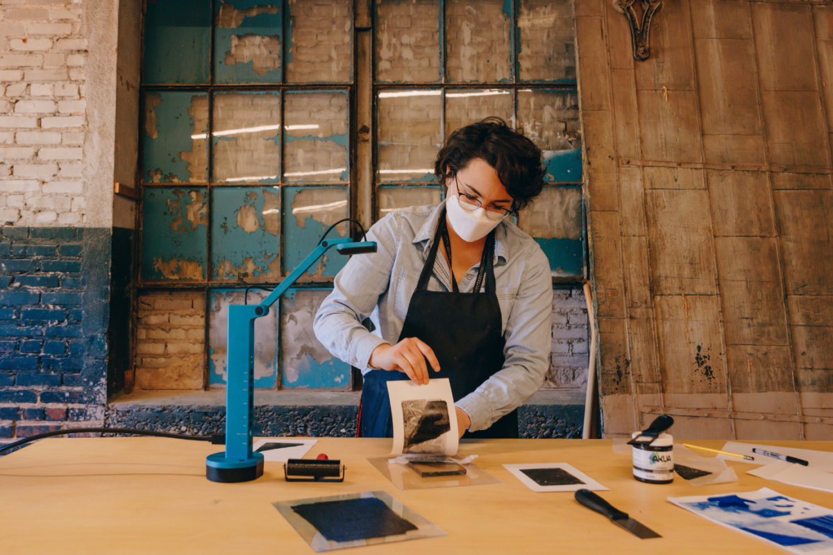 Woman in an apron creating artwork at a desk