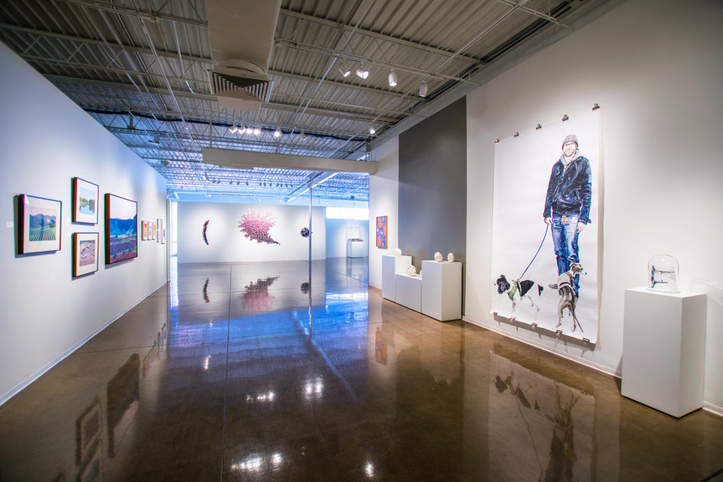 Various pieces of art line the white walls of a gallery with shiny waxed concrete floors