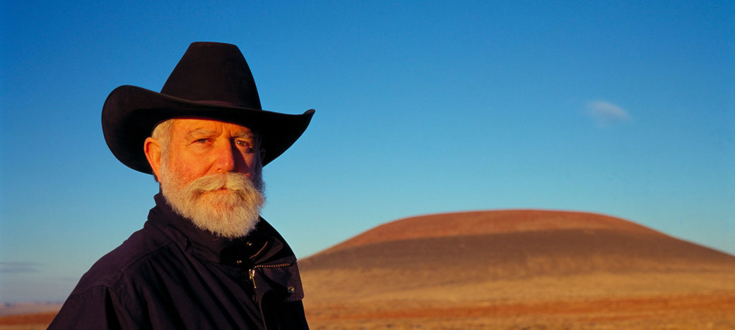 A figure with a white beard and black cowboy hat poses for a photo in front of a prairie mesa on a cloudless day