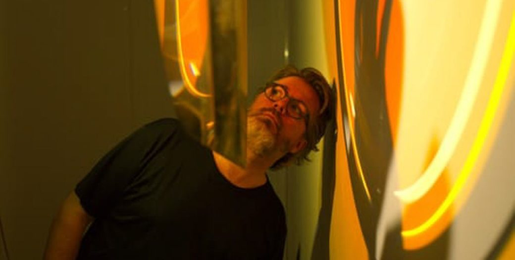 A figure in glasses cranes their neck to thoughtfully examine a light sculpture emitting a yellow light