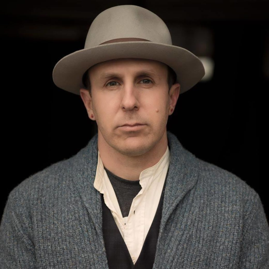 A person wearing a wide-brimmed hat looks directly into the camera