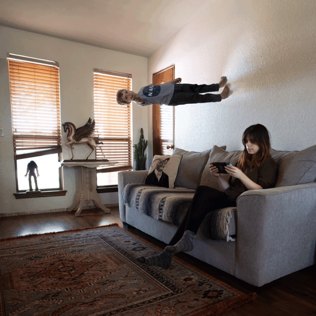 An adult sits on a couch holding an electronic device while a child stands upright on the wall, pointing at the camera