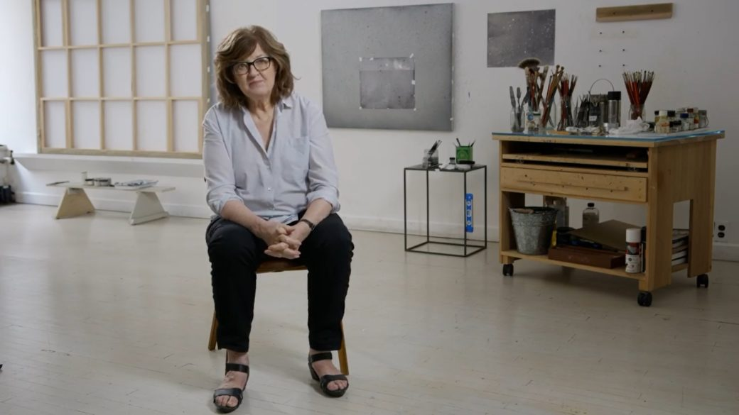 A person with arms crossed sits in an art studio surrounded by supplies and their work