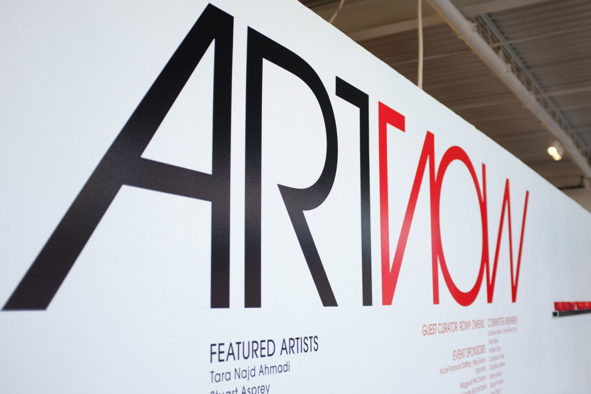 """A logo saying """"ARTNOW"""" painted on a white wall in red and black"""