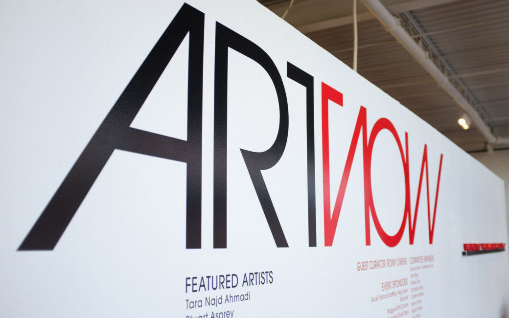 "A logo saying ""ARTNOW"" painted on a white wall in red and black"