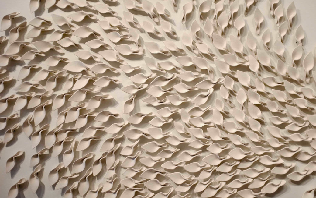 An all-tan, wall-mounted sculpture depicting a swirling cluster of ceramic leaves