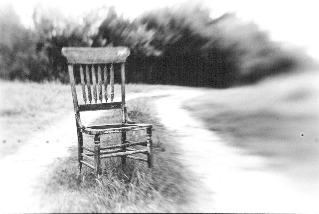 In a black and white photograph a chair sits along a grass and dirt path, background is blurred