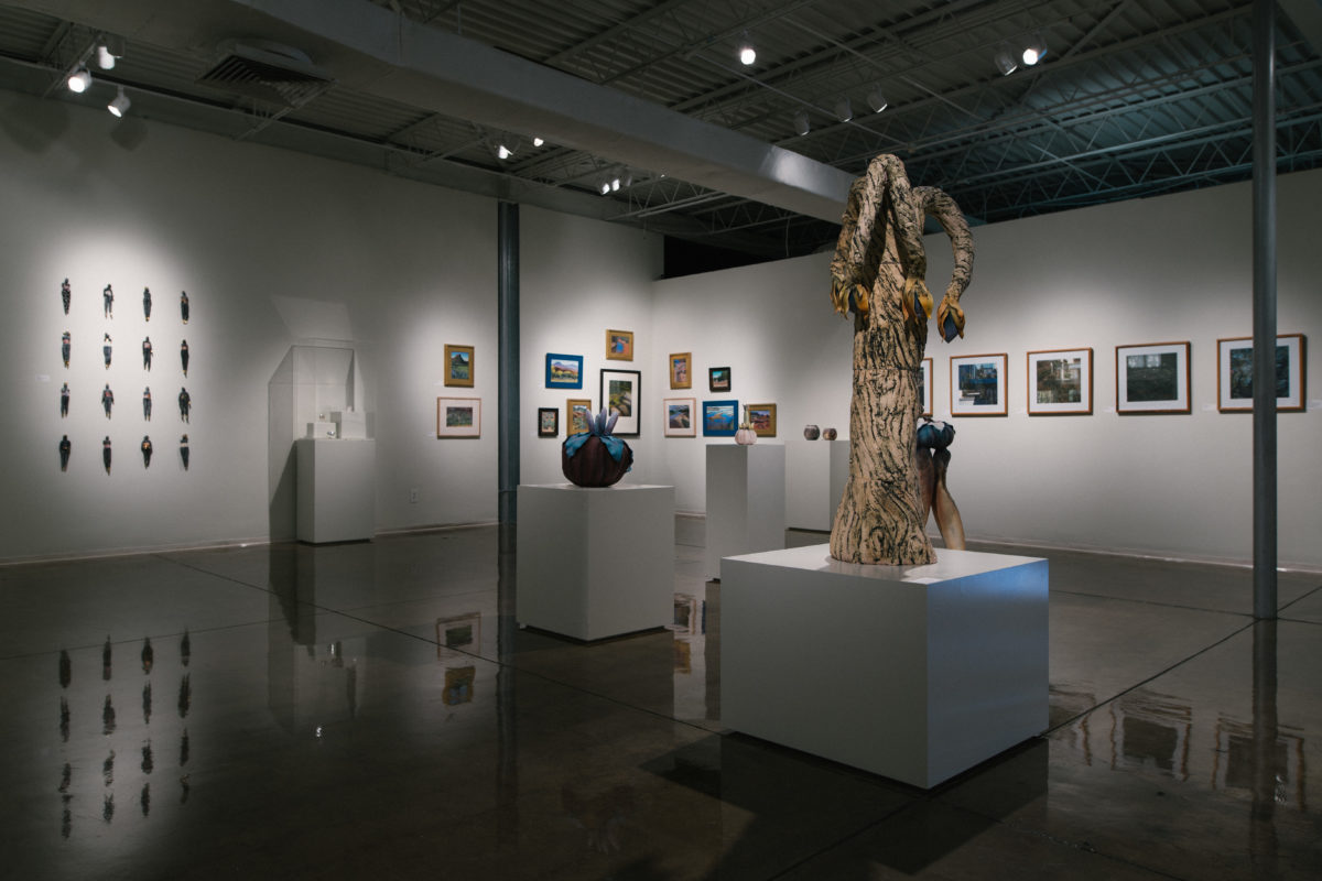 A white gallery filled with various sculptures and wall hangings