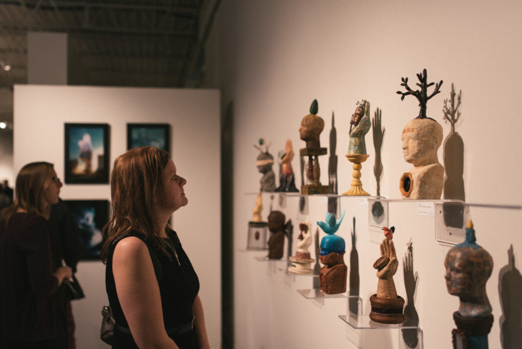 A woman gazes at various miniature sculptures of abstract hands and heads mounted on a wall on clear plastic shelves
