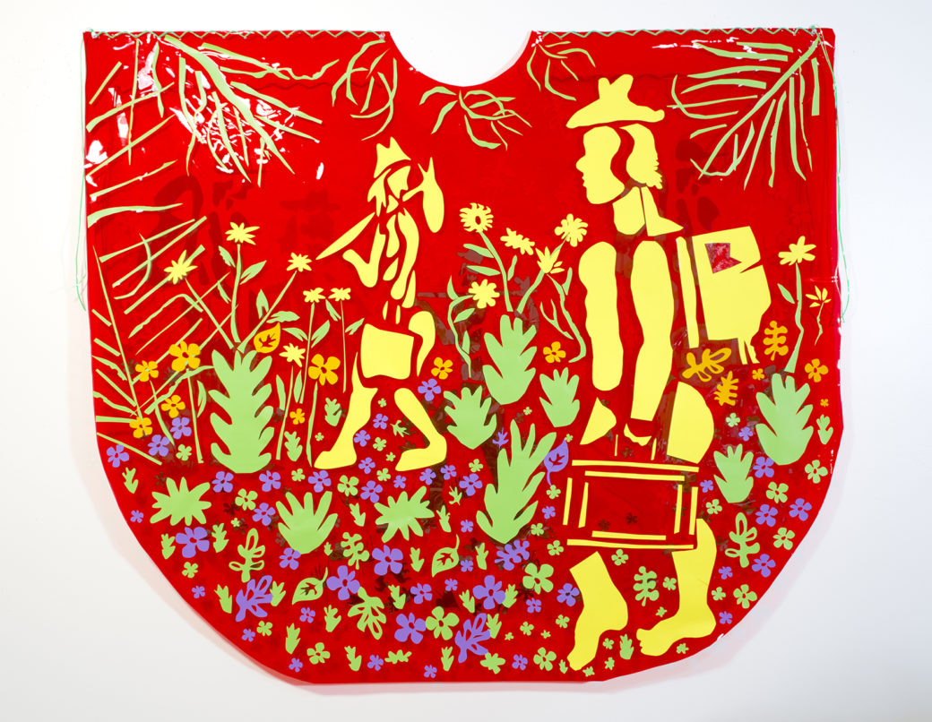 A 2-D mixed-media sculpture features a red background with woodcut-style images of yellow figures walking amid flowers and plants