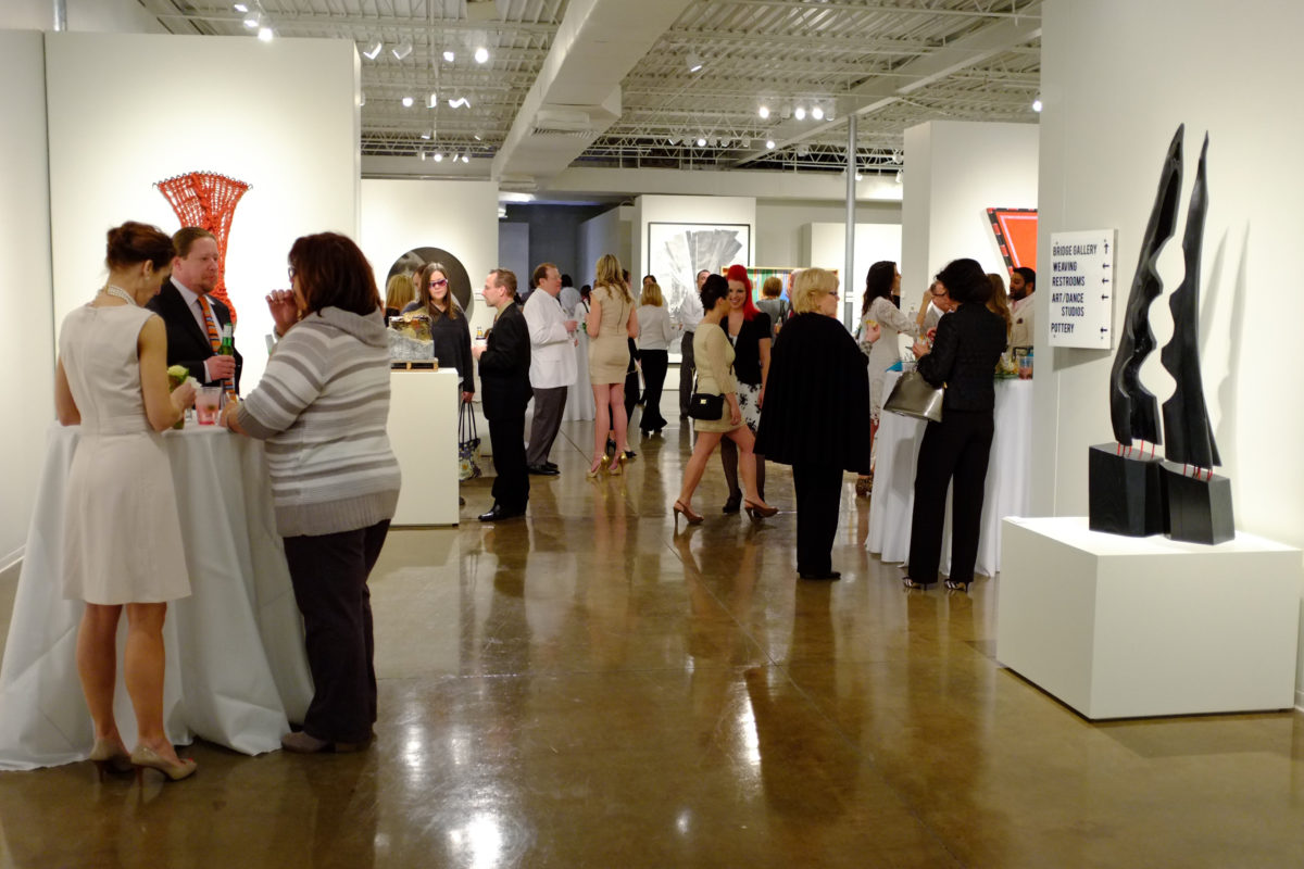 A crowd of men and women gather in a gallery space with various sculptures