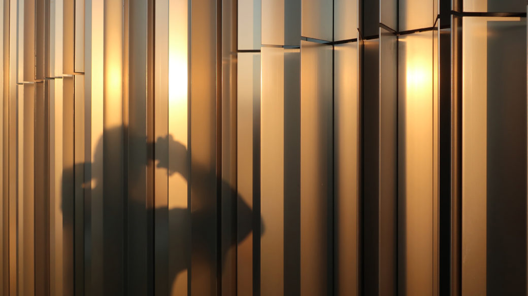 A photographer is reflected in shadow on a metal building turned golden by the sun