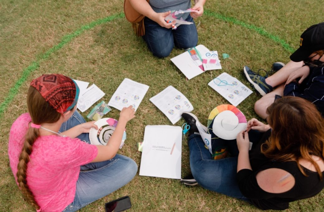 A group of people sit in the grass and work on a craft project