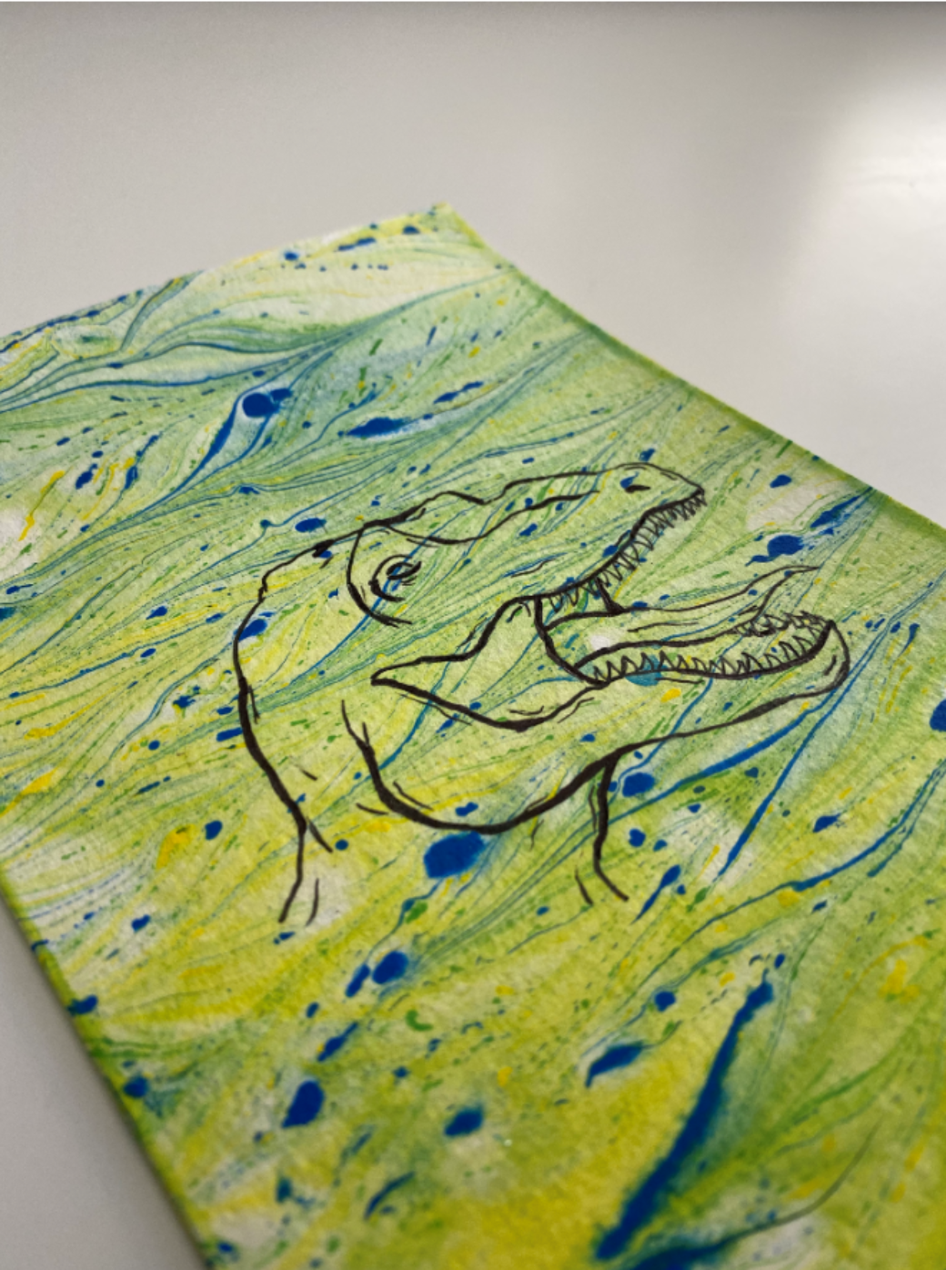 A colorful homemade work of art depicts a tyrannosaurus rex with its tongue sticking out