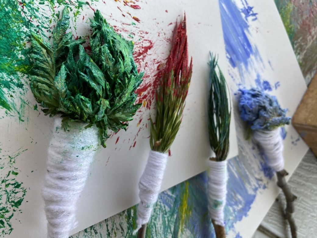 Four paintbrushes made with natural materials and dipped in colorful paint