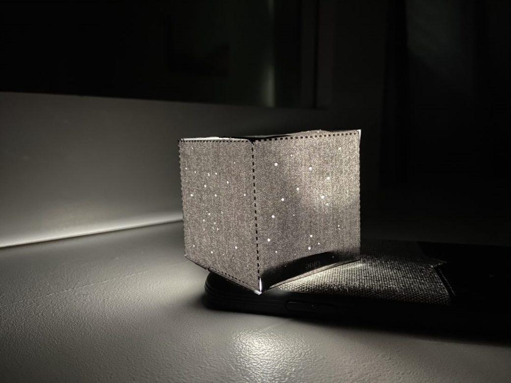A small, square, paper sculpture rests on a phone flashlight illuminating a dark corner