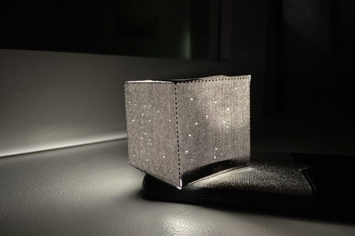 A square object made of fabric with a light in the middle, creating the impression of a starry night sky