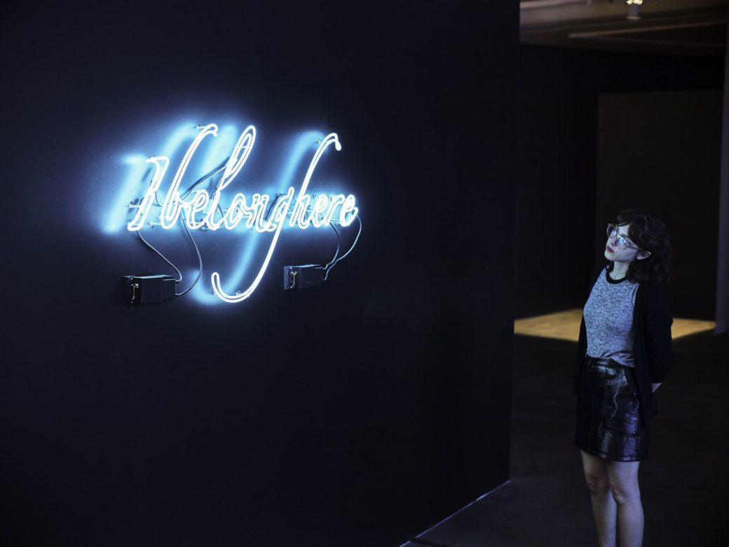 "A figure stands in front of a neon sculpture spelling the words ""I belong here"""