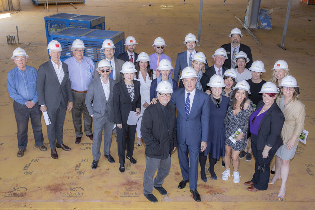 A group of men and women in business attire and hard hats stand in a construction site