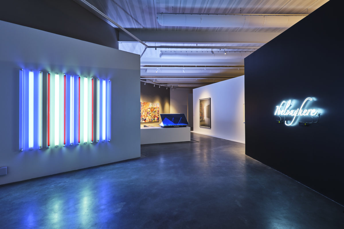 Art gallery featuring two light works (on a white wall, one on a black), a sculpture and two hanging works