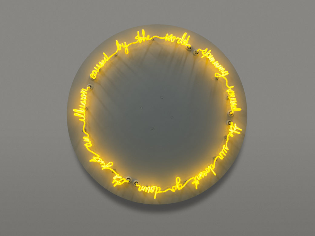 """Glowing yellow neon words saying """"The sun don't go down/it's just an illusion/caused by the world/spinning round"""" form a circle"""