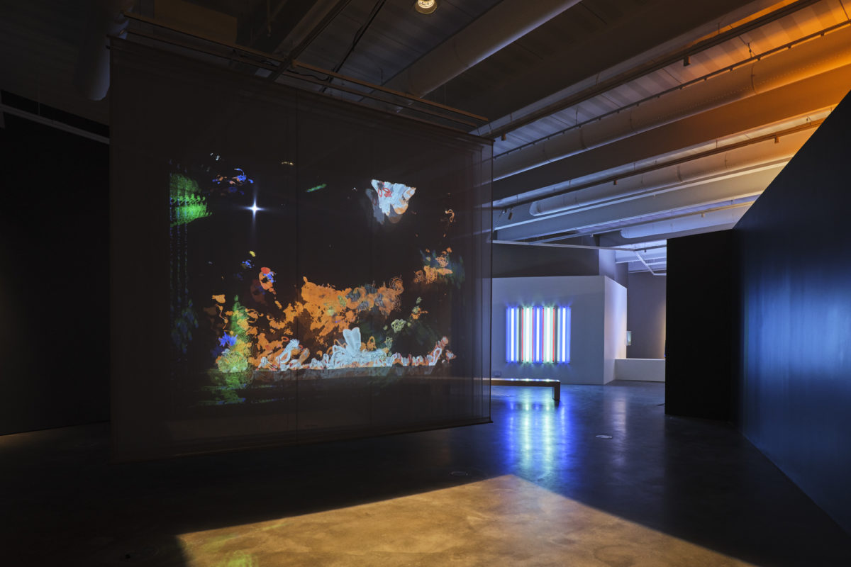 Interior view of an art gallery with an abstract light sculpture in the foreground