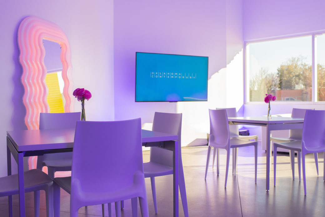 A clean room with lots of natural sunlight, including a vibrant pink art mirror, purple tables and chairs and TV screen displaying the Oklahoma Contemporary logo
