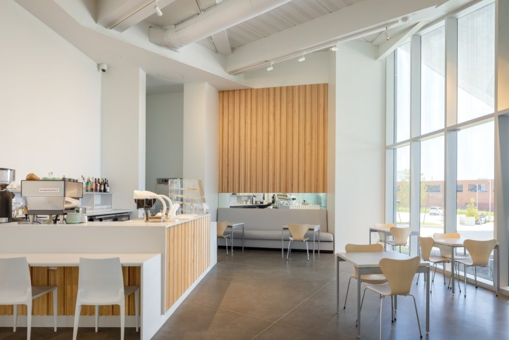 A cafe with white walls, wooden panels and large windows stands empty
