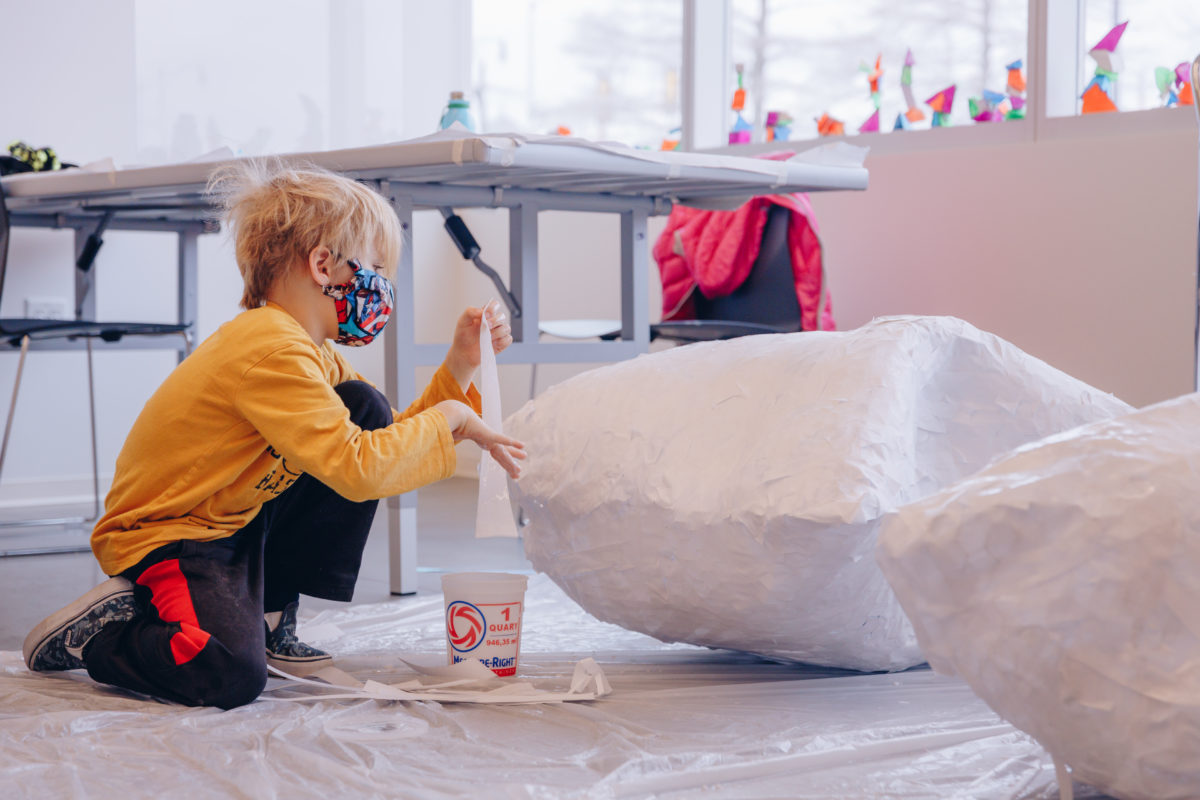 A child in a mask and a yellow shirt works on a large white sculptural piece in a studio