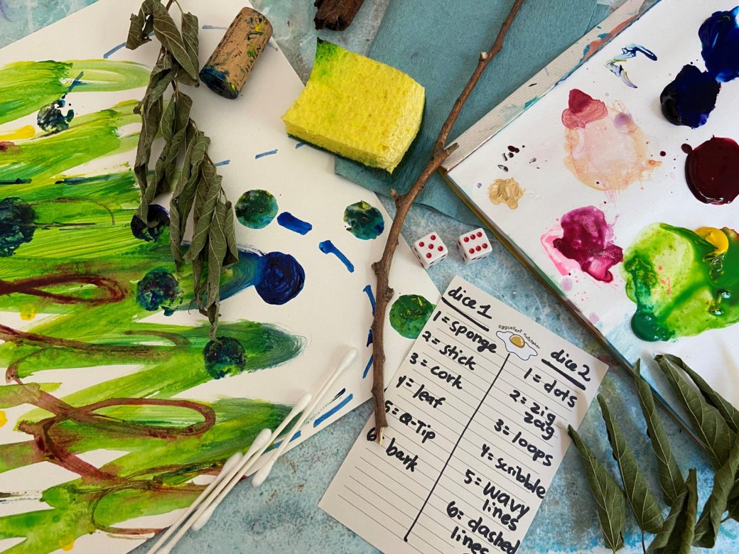 Scattered improvisational art supplies like sponges, leaves and twigs, alongside abstract painting and handwritten materials