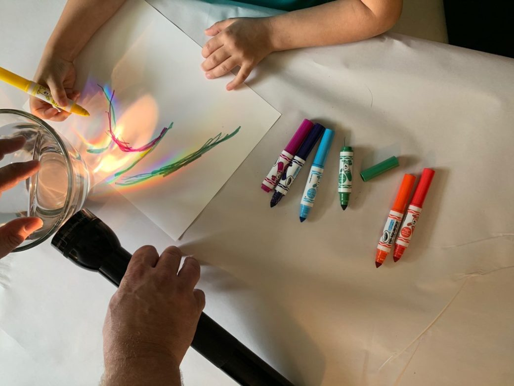 A child's hands draw with magic markers, while adult hands hold a flashlight up to a glass of water to create a colorful effect