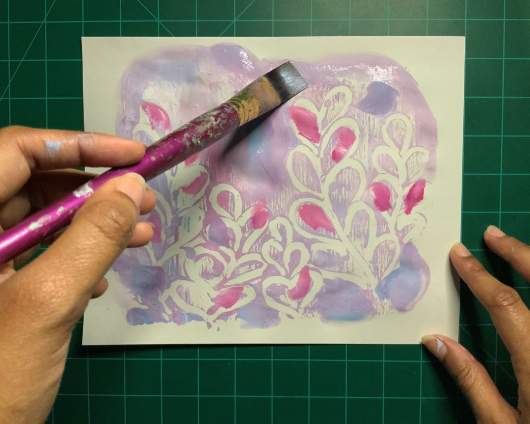 Hands paint a floral design in purple and punk pastels