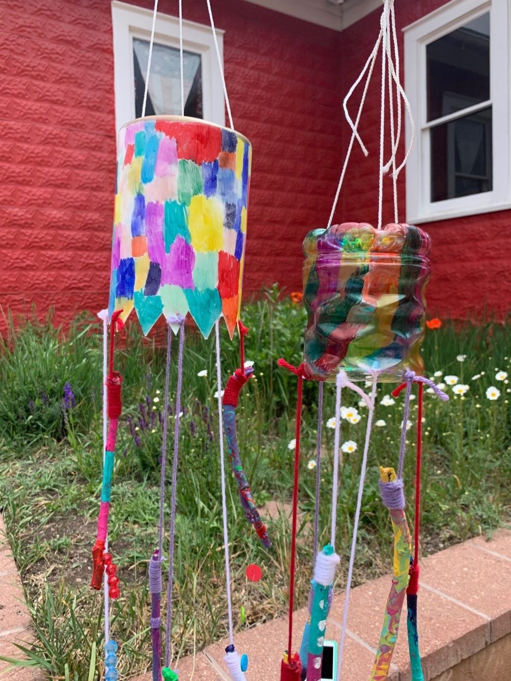 Two colorful outdoor sculptures hang vertically in front of a red house