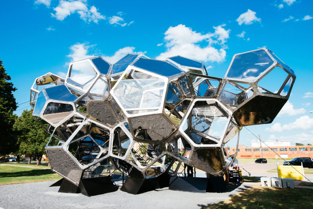 A large-scale glass and metal sculpture of hexagonal cubes stands on gravel in a park