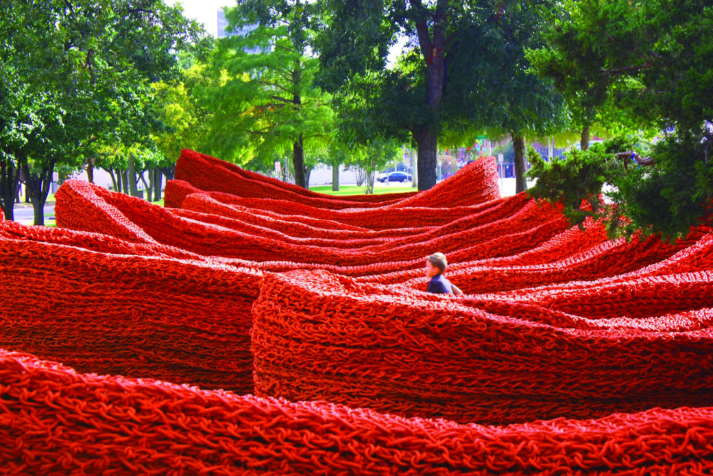 A child walks through a winding large scale knit fabric installation outside with trees in the background