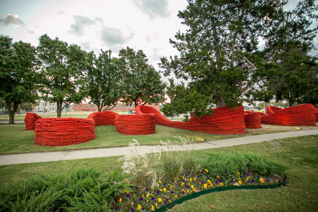 A green park with a large red rope sculpture winding through the trees
