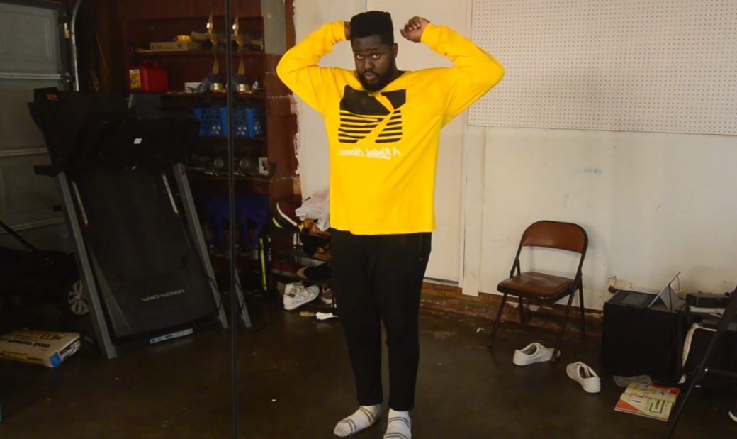 A man in a yellow sweatshirt and black pants dances in a home garage space